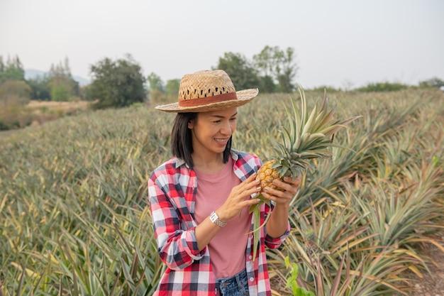 アジアの女性農民は農場でパイナップルの成長を見ます、若いきれいな農夫の女性は農地に立っています。