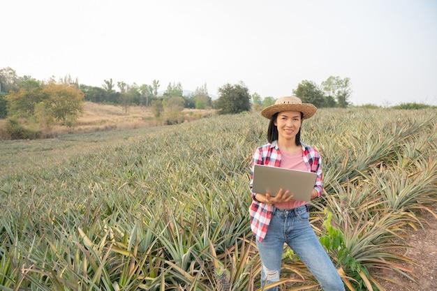 L'agricoltore femminile asiatico vede la crescita dell'ananas nella fattoria. industria agricola, concetto di affari di agricoltura.