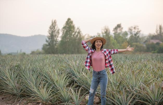 L'agricoltore femminile asiatico vede la crescita dell'ananas in fattoria, giovane donna graziosa del coltivatore che sta sul terreno coltivabile con le braccia alzate su felicità euforica gioiosa.