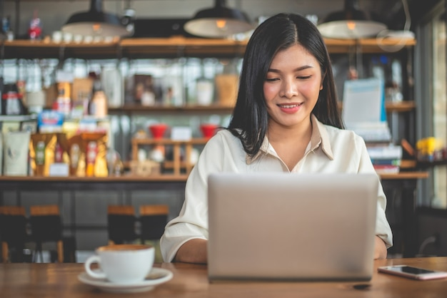 Asian female freelancer smiling when using laptop in cafe. business and success
