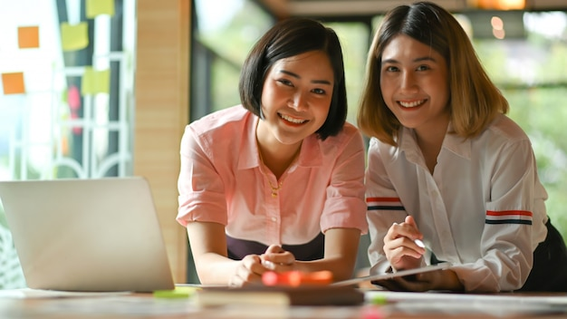 Asian female graphic designer working together at the office they use laptop and tablet.