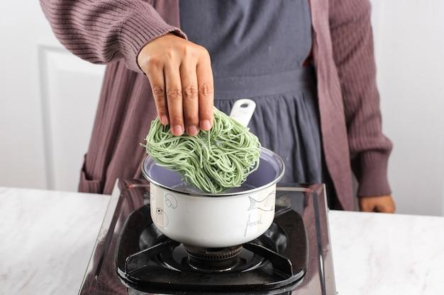 Азиатская женская рука, варящая зеленые овощи, корейская лапша быстрого приготовления на сковороде, добавление лапши в сковороду, домашнее приготовление