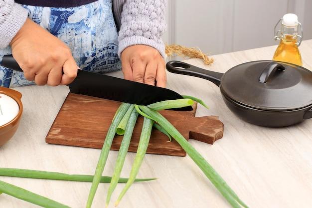 木製のまな板に黒いナイフを使用して、キッチンで段階的に調理するアジアの女性の手でネギを切る