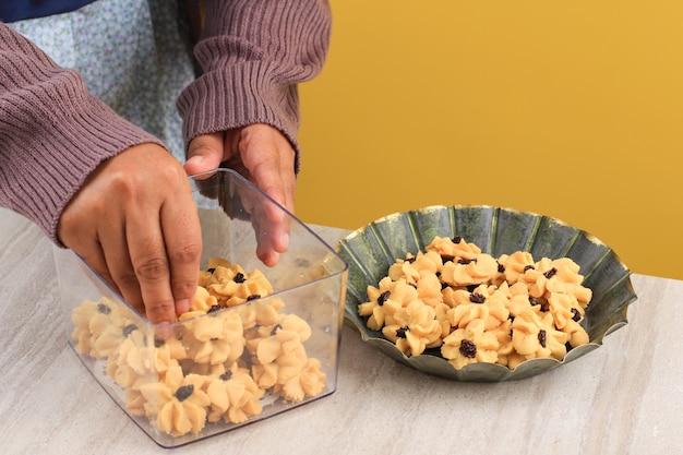 アジアの女性の手がクリアボックスにkuekering(cookies)を置き、販売の準備ied mubarak kuelebaran。ボックスにiedcookieを配置します。テキスト用のコピースペース