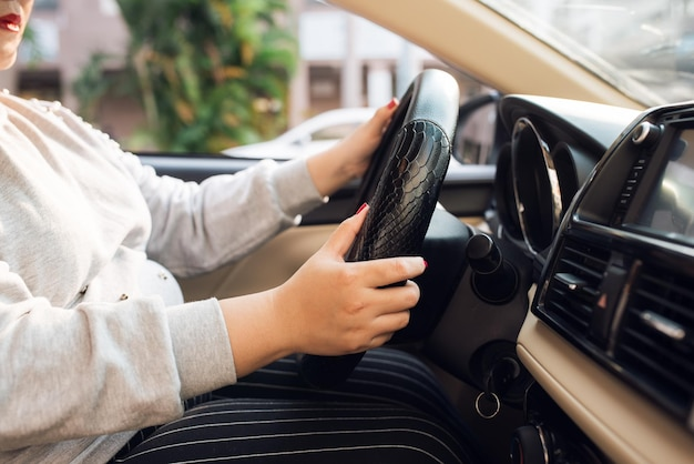 앞유리와 도로를 운전하는 동안 아시아 여성이 자동차 운전대를 잡고 있습니다. 흑인 여성이 자신있게 운전대를 잡고 있습니다. 바퀴에 손 - 자동차를 운전하는 여성 - 아시아