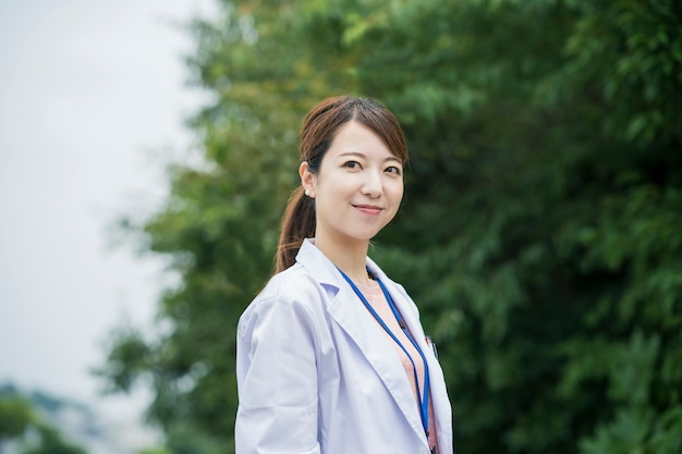 Asian female healthcare worker in white coat