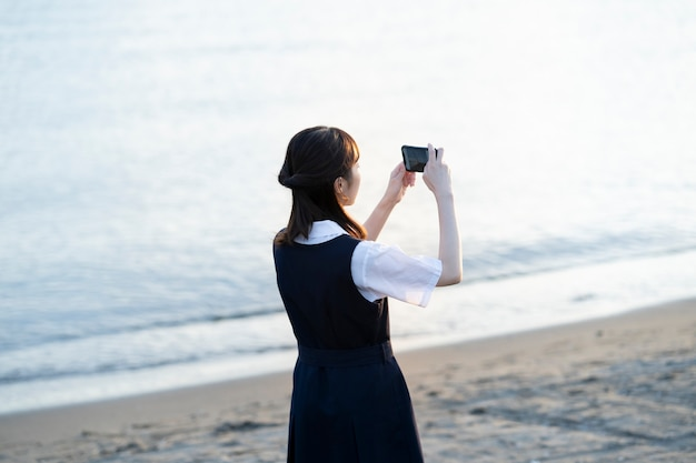 Asian female high school student taking pictures of scenery with a smartphone