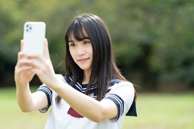 Asian female high school student touching the screen of smartphone