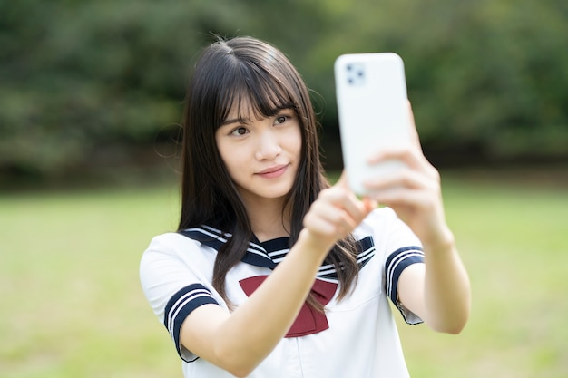 Азиатская студентка средней школы, касаясь экрана смартфона
