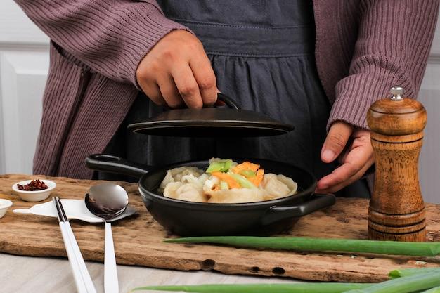 アジアの女性ホームシェフが点心スープを調理するマンドゥグク、ネギのトッピングとストーブの上にスライスした目玉焼きを添えた韓国の餃子スープ。スライスしたネギを入れる