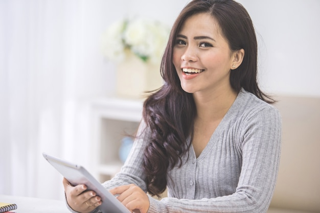 Asian female at home using tablet