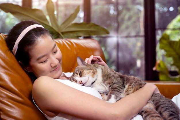 아시아 여성 소파에 고양이 포옹