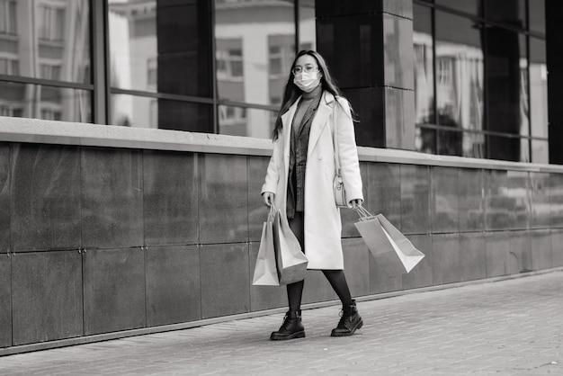 コート、眼鏡、医療用マスクを身に着けたアジア人女性が、荷物を手に持って通りに立っています。