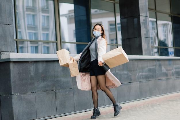 Азиатская женщина в пальто, очках и медицинской маске стоит на улице, держа в руках пакет.