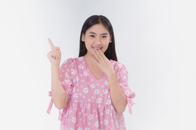 ピンクのドレスを着たアジアの女性はエキサイティングな行動をし、白い背景に何かを提示するように指しています。