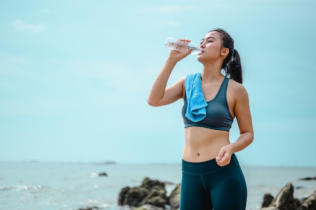 Asian female jogger drinking fresh water after trainingyoung athletic woman exercising on the rocks