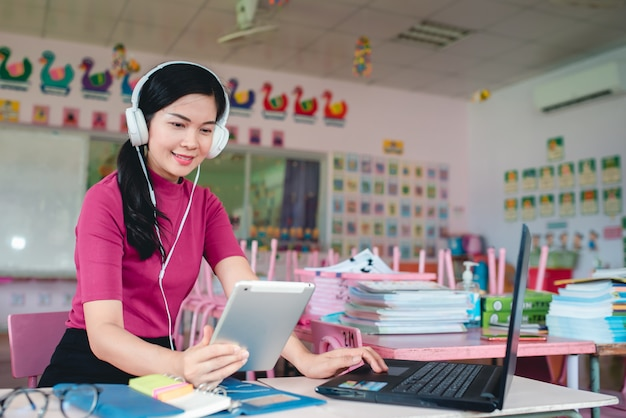 Asian female kindergarten teacher is teaching kindergarten students online. teachers and students use online video conferencing systems to teach students.