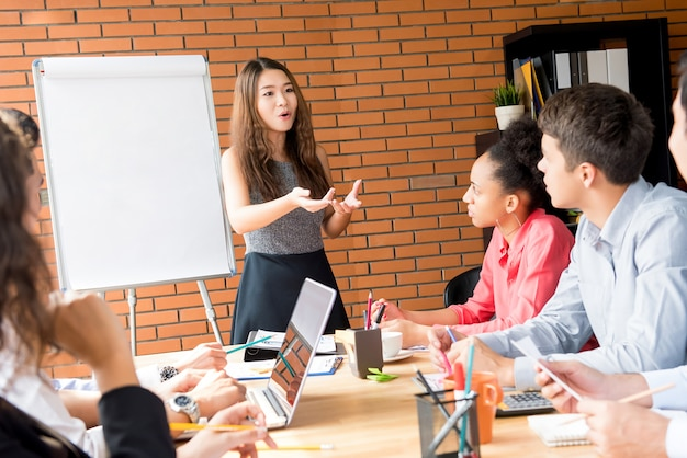 Asian female leader presenting work the in meeting