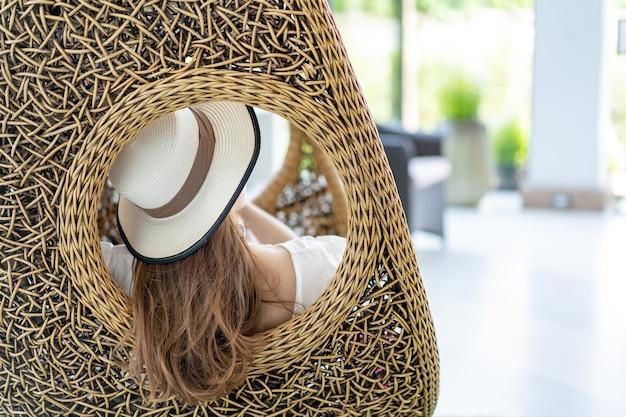 Азиатская женщина с длинными каштановыми волосами в плетеной шляпе сидит и отдыхает в кресле-вешалке на курорте таиланда.