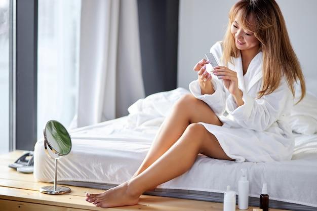 週末に、明るい寝室でファイルでマニキュアを作るアジアの女性。コロナウイルスの流行のために自宅でシャワーを浴びた後の女性。家庭生活
