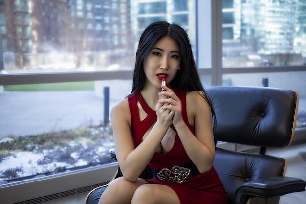 아시아 여성 모델은 유행 섹시한 빨간 드레스를 입고있다