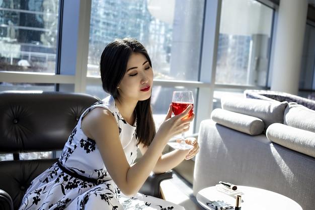 아시아 여성 모델은 세련된 섹시한 흰색 드레스를 입고있다