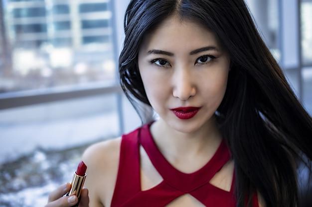Modello femminile asiatico indossa un vestito rosso sexy alla moda
