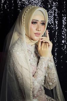 아시아 여성 모델은 간단한 인도네시아 이슬람 전통 웨딩 드레스를 입는다
