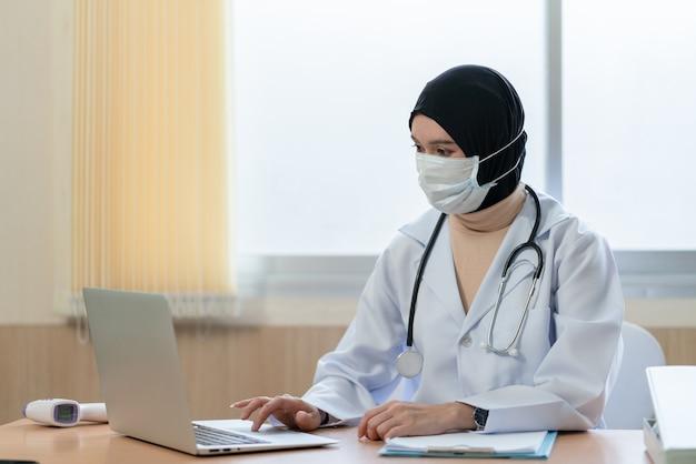 病院でラップトップで働くフェイスマスクを身に着けているアジアの女性のイスラム教徒の医師
