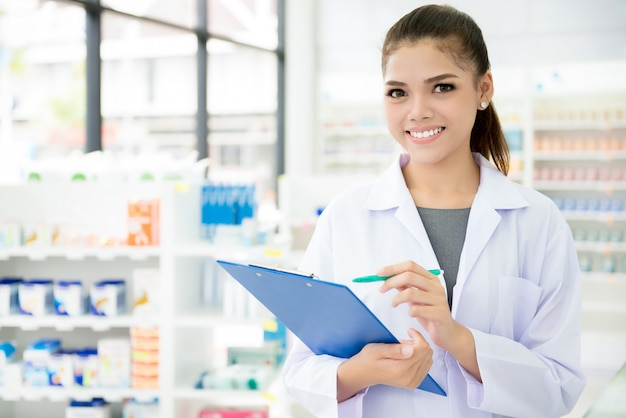 Asian female pharmacist working in chemist shop or pharmacy