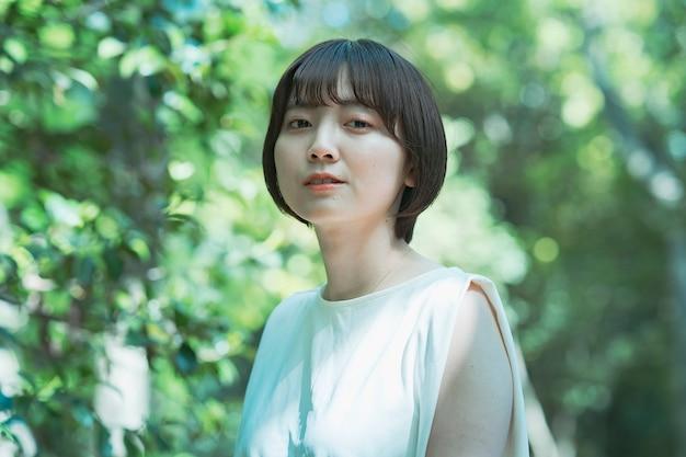 晴れた日の森の中でアジアの女性のポートレート