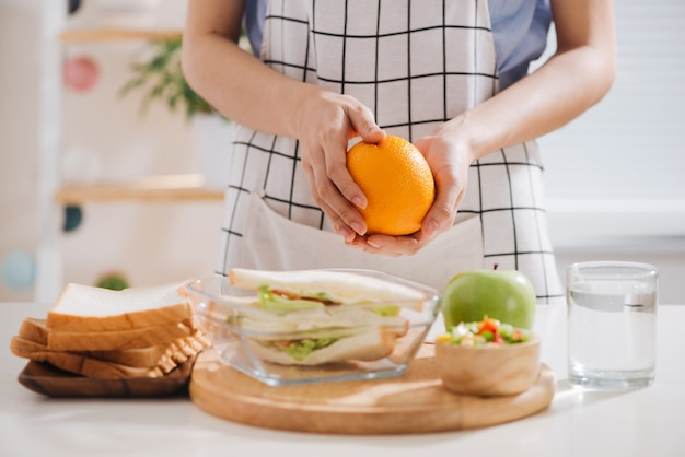 Asian female preparing food (fruits and vegetables) for healthy eating child (kid).