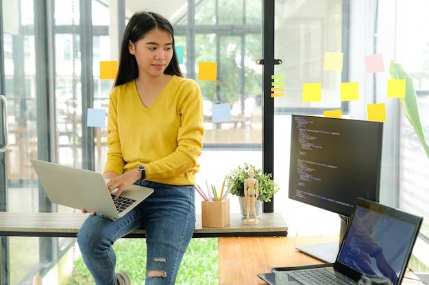 黄色のシャツのアジア女性プログラマーは棚の上に座って、脚にラップトップを置きます。彼女はテーブルのコンピューター画面を見つめて考えました。