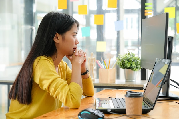 彼女のあごに手で座っている黄色のシャツのアジアの女性プログラマーは、コンピューターの画面を見つめ、熟考しました。