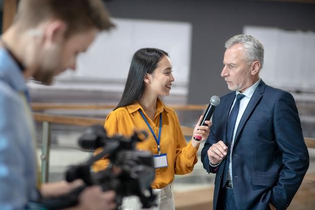 Азиатская женщина-репортер держит микрофон в руке во время разговора с бизнесменом