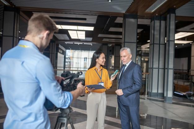 Азиатская женщина-репортер стоит рядом с седым мужчиной во время интервью у него