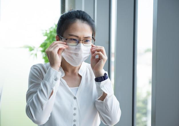 Азиатское женское серьезное мышление и носить маски в модельном офисе смотрят в окно