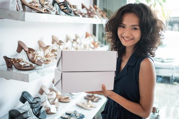 Азиатский женский продавец с обувными коробками в магазине