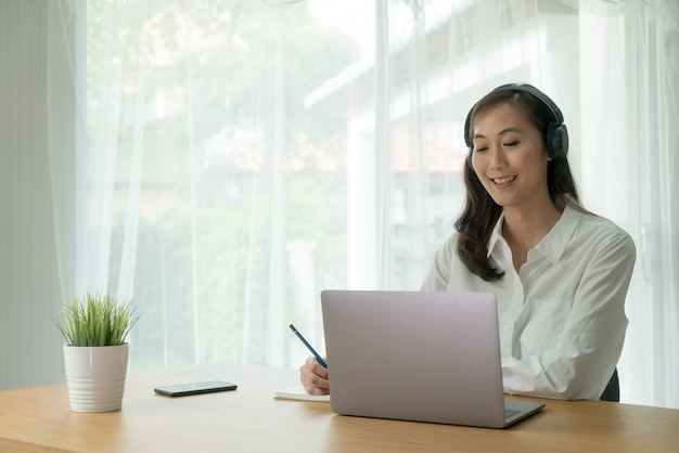 Asian female smiling and video call online from laptop notebook computer waring wireless headphone and making notes at the desk.
