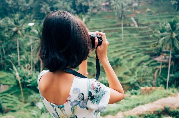 Asian female solo travelers photograph tegalalang rice terrace, ubud, bali, indonesia