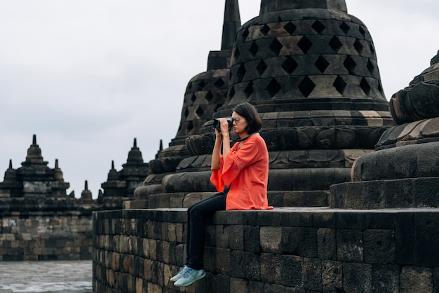 Asian female solo travelers take photo ancient buildings at borobudur temple, java, indonesia