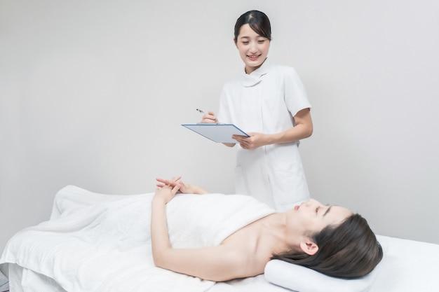 Азиатский женский персонал в косметическом салоне дает консультации