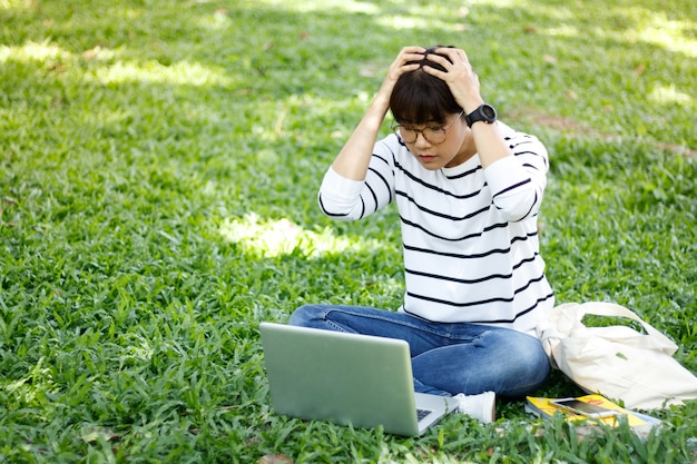Asian female student doing her homework in confusion while sitting in a university campus.