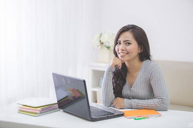Asian female student at home studying using laptop