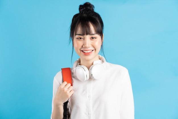 背中の後ろにバックパックを背負って、スマートフォンを持って、ワイヤレスイヤホンを身に着けている首、紙コップを持っているアジアの女子学生 Premium写真