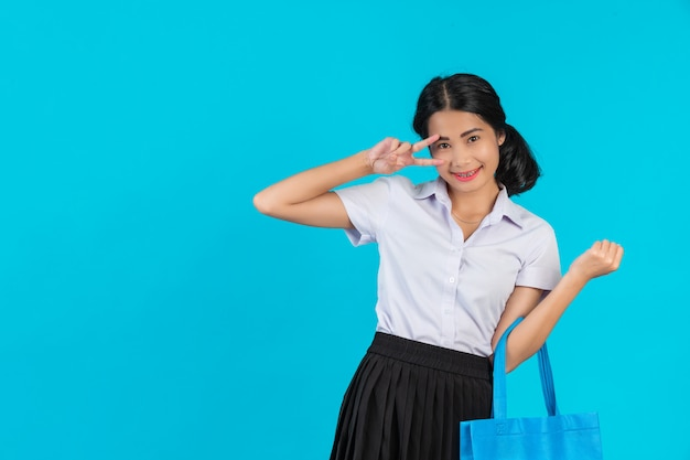 An asian female student who spins a cloth bag and shows various gestures on a blue .