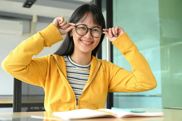Asian female student with glasses and smiled for the camera. she is reading exam preparation books.