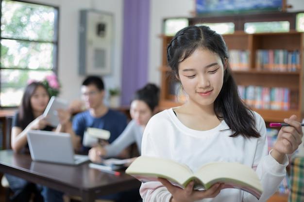 도서관에서 선택 책을 들고 아시아 여자 학생