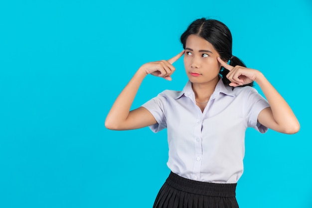 Asian female students performing various gestures on a blue .