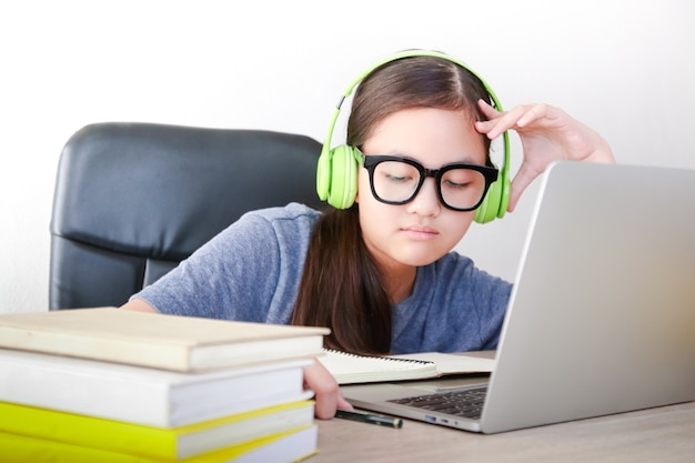 아시아 여학생들은 집에서 온라인으로 공부합니다. 공부의 스트레스에 앉아보세요. 사회적 거리의 개념, 교육을위한 기술 사용.